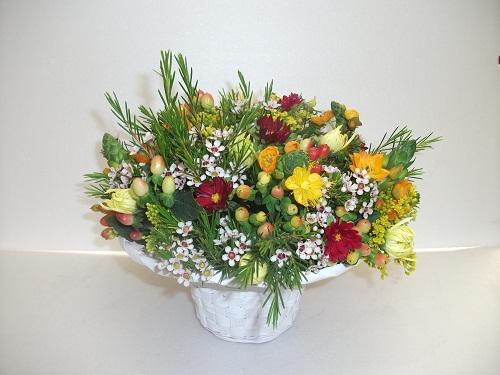 סידור שולחן טבעי עם אסטר, פרח שעווה, פרח, נץ חלב וחרציות